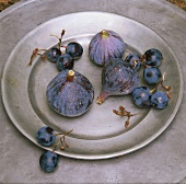 Figs and blue grapes on pewter plate