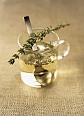 Thyme in a water glass with a spoon