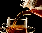 Pouring black tea from a pot into a glass cup