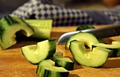 Thick cucumber slices on a wooden platter with a knife