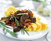 Lamb goulash with rosemary and ribbon noodles on plate