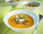 Orange and carrot cream soup with mackerel and chives