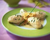 Salmon dumplings in chive sauce on plate