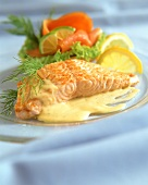 Fried salmon fillet with sauce and salmon roll on plate