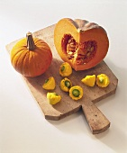 Various types of pumpkin and squash on chopping board