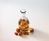 Walnut oil in a carafe, walnuts in front
