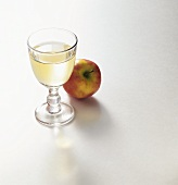 A glass of vinegar and an apple