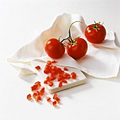 Vine tomatoes & diced tomatoes on cloth & chopping board