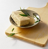 Smoked tofu in a bowl on chopping board