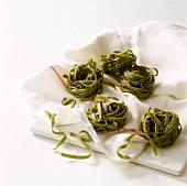 Green tagliatelle on tea towel