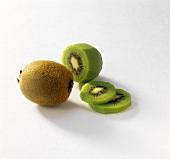Unpeeled kiwi, half peeled kiwi and kiwi slices