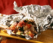 Hare with tomatoes, onions and olives in foil