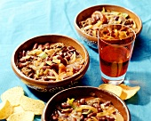 Chili con carne in earthenware dishes; red wine; tortilla chips