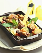 Chicken pieces on vegetable gratin in roasting dish