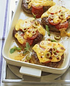 Vienna steaks gratinated with cheese, olives and tomatoes