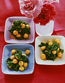 Chick-pea and spinach salad on small plates; red carnations