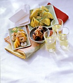 Various tapas in bowls on cloth; three sherry glasses