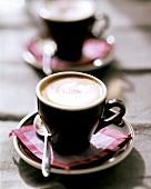 Cappuccino in brown espresso cups