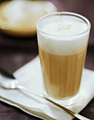 Latte macchiato in a glass on a napkin