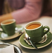 Espresso in two pale green cups on table