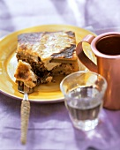 Moussaka on yellow plate and fork; wine; copper jug