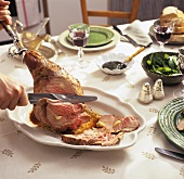 Carving leg of lamb on laid table