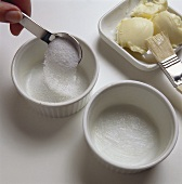 Sprinkling sugar in buttered dessert moulds