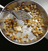 Tossing croutons in butter