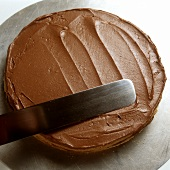 Spreading chocolate cream on a cake