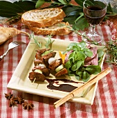 Poultry liver kebabs with salad, bread and red wine