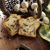 Zwei Scheiben Champignonkuchen vor Korb mit Champignons