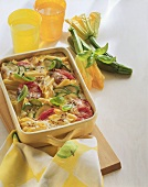 Courgette & pasta bake with tomatoes & basil in baking dish