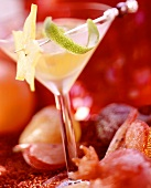 Champagne sangria in glass, surrounded by candied fruit
