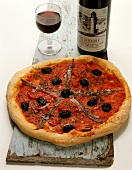 Pizza with anchovies and olives; red wine