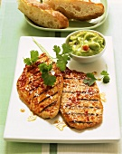 Grilled turkey escalope; avocado sauce in bowl; bread