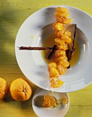 Kumquat chain with cinnamon sticks in orange sauce