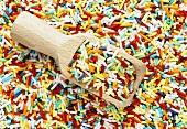Bunte Zuckerstreusel mit Holzschaufel (bildfüllend)