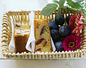Plum cake, fresh plums and flowers in bread basket