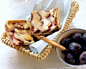 Plum cake with quark on tray; fresh plums