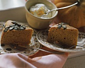 Two pieces of pumpkin cake with pumpkin seeds; cream in bowl