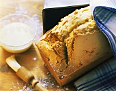 Madeira cake beside loaf tin; icing and pastry brush