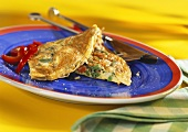 Vegetable omelette on blue plate with cutlery