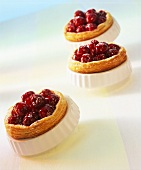 Cherry tarts with icing sugar in the baking tins