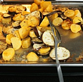 Turning roasted vegetables in the oven