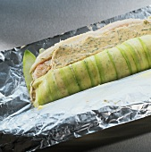 Rolling up salmon and plaice roulade in aluminium foil