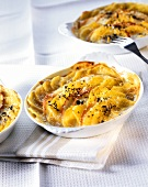 Casserole with potatoes and apples in baking dish