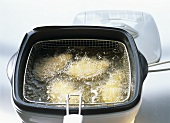 Deep-frying breaded chicken pieces