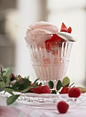 Rose ice cream with raspberries & strawberries in glass; spoon