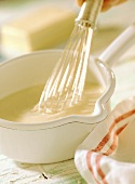 Bechamel sauce in pan with whisk