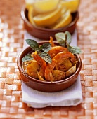 Shrimps with tomato and saffron sauce in terracotta bowl